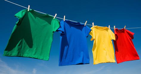 Grupo de 4 camisetas com cores primárias extendidas para secar no varal com fundo de céu azul